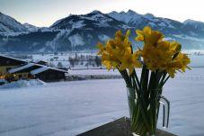 Blumen am Balkon von Mountain View apartment in Kaprun, Österreich mit schneebedeckten Bergen im Hintergrund